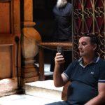 Mann blickt auf sein Mobiltelefon in der Kirche