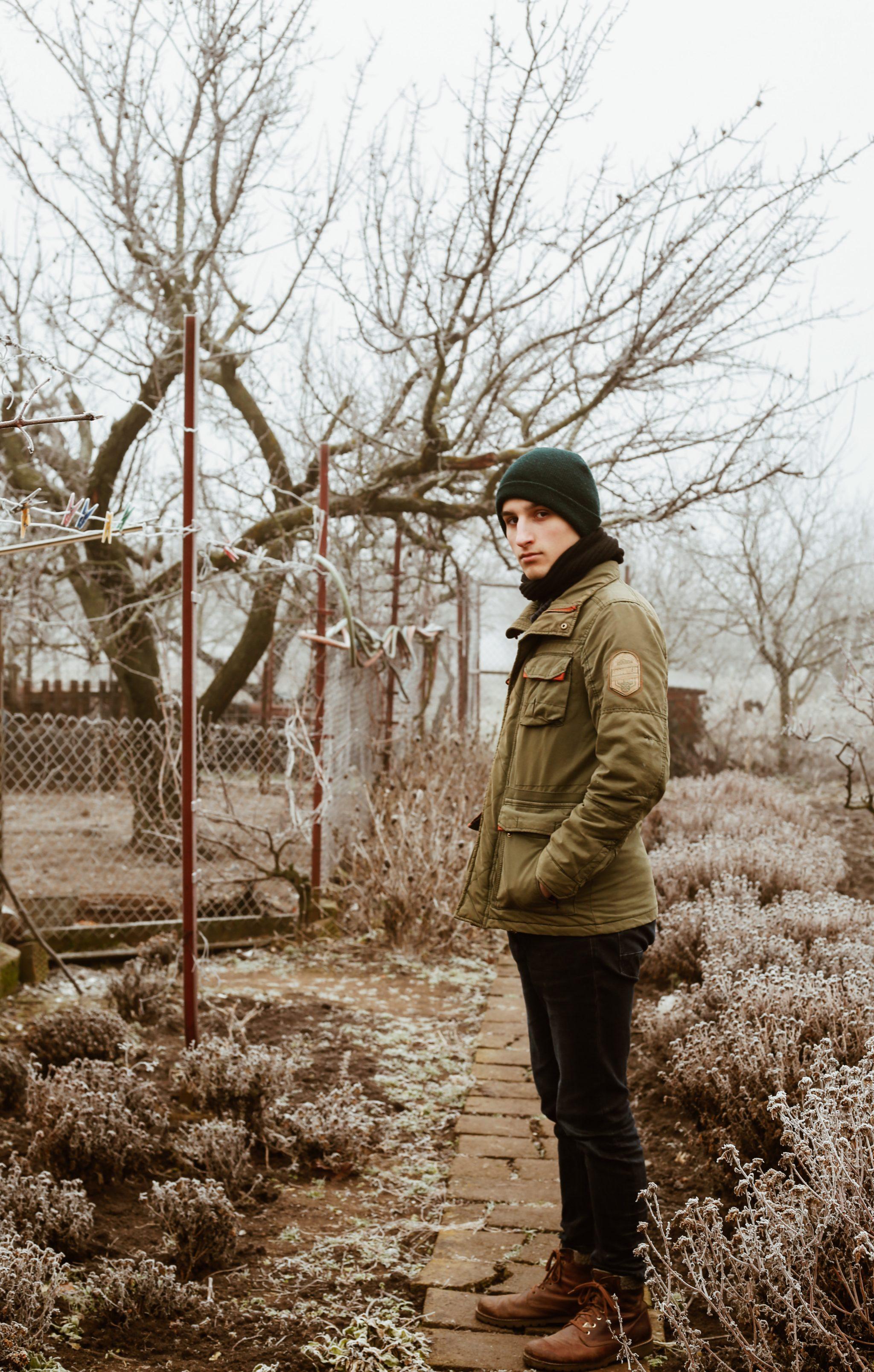 Junger Mann im winterlichen Garten